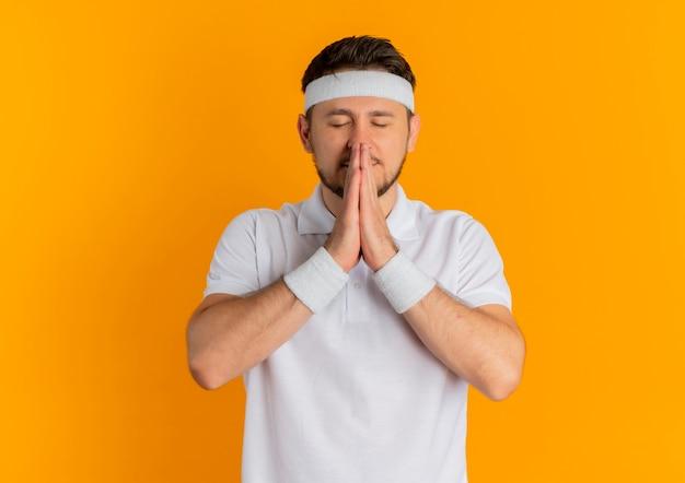 오렌지 배경 위에 서 희망 식으로 닫힌 된 눈과 함께 손을 잡고 머리띠와 흰 셔츠에 젊은 피트 니스 남자