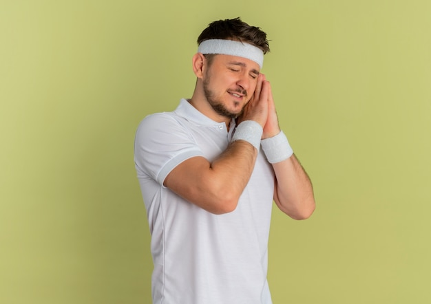 닫힌 된 눈을 가진 손바닥에 머리를 기울고 함께 머리를 들고 머리띠와 흰 셔츠에 젊은 피트 니스 남자는 올리브 배경 위에 서 자고 싶어