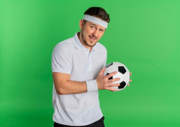 녹색 배경 위에 유쾌하게 서있는 카메라를보고 축구 공을 들고 머리띠와 흰 셔츠에 젊은 피트 니스 남자