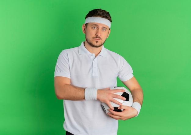 녹색 배경 위에 서있는 자신감이 식으로 카메라를보고 축구 공을 들고 머리띠와 흰 셔츠에 젊은 피트 니스 남자