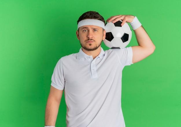 녹색 배경 위에 서 심각한 얼굴로 카메라를 찾고 어깨에 축구 공을 들고 머리띠와 흰 셔츠에 젊은 피트 니스 남자