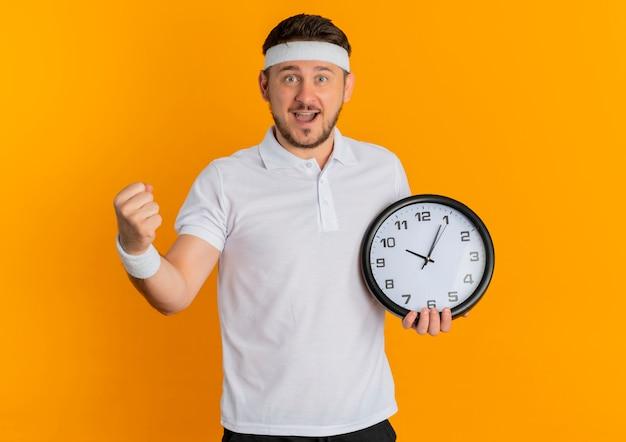 オレンジ色の背景の上に立って幸せで興奮した拳を握り締める壁時計を保持しているヘッドバンドと白いシャツの若いフィットネス男
