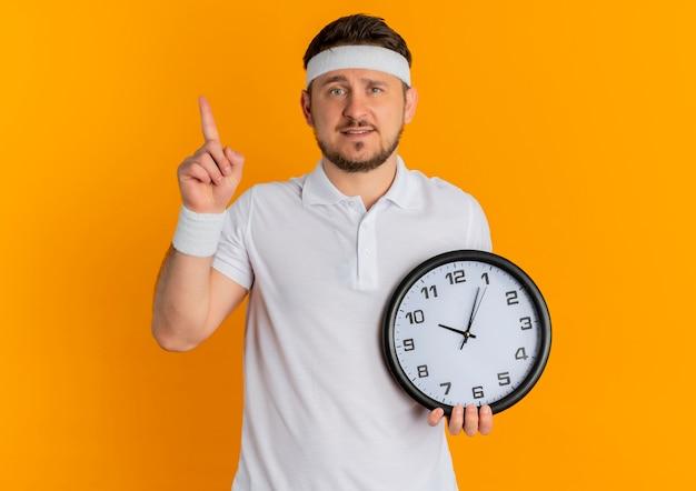 オレンジ色の背景の上に立っている顔に笑顔でカメラを見て指で上向きの壁時計を保持しているヘッドバンドと白いシャツの若いフィットネス男