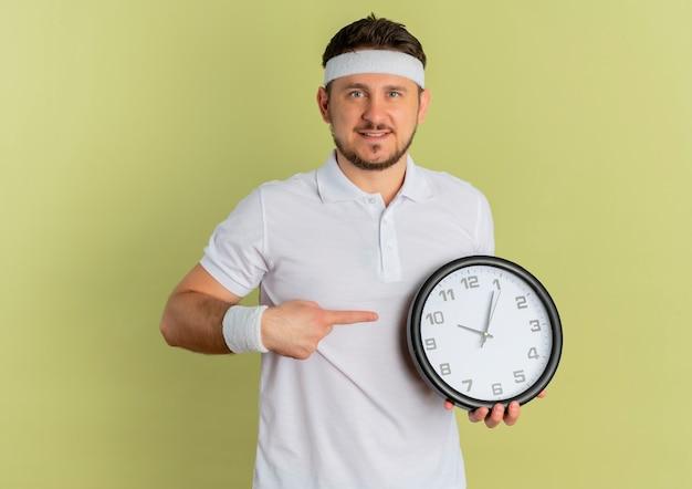 オリーブの背景の上に立って自信を持って笑ってそれに指で指している壁時計を保持しているヘッドバンドと白いシャツの若いフィットネス男