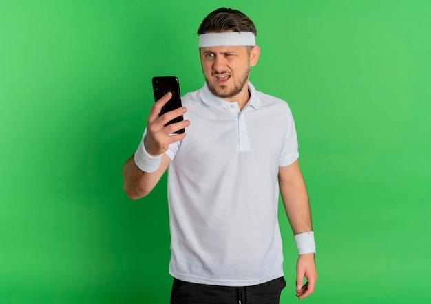 緑の壁の上に立っている混乱した表情で彼の携帯電話の画面を見ているヘッドバンドと白いシャツを着た若いフィットネス男