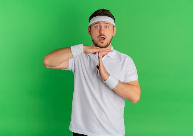 Молодой фитнес-мужчина в белой рубашке с повязкой на голову, глядя вперед, делая жест тайм-аута с удивленными руками, стоя над зеленой стеной