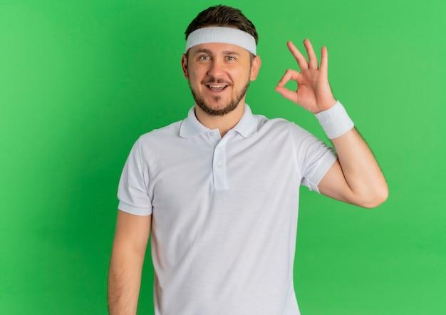 Молодой фитнес-мужчина в белой рубашке с повязкой на голову, глядя вперед, весело улыбаясь, делает хорошо, поет, стоя над зеленой стеной