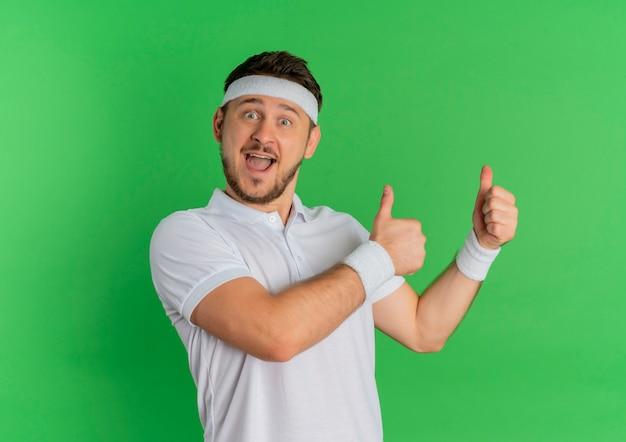Молодой фитнес-мужчина в белой рубашке с повязкой на голову, глядя вперед, весело улыбаясь, показывает палец вверх, стоя над зеленой стеной