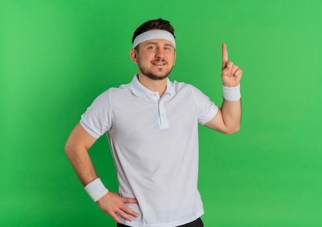 Молодой фитнес-мужчина в белой рубашке с повязкой на голову, глядя вперед, улыбаясь, уверенно указывая пальцем вверх, стоя над зеленой стеной