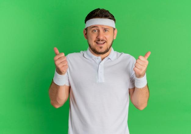 Молодой фитнес-мужчина в белой рубашке с повязкой на голову, глядя вперед, улыбаясь, показывает палец вверх, стоя над зеленой стеной