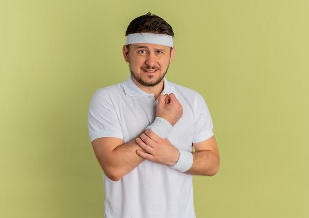 オリーブの壁の上に立って痛みを抱えている彼の手首に触れて正面を向いているヘッドバンドを持つ白いシャツの若いフィットネス男