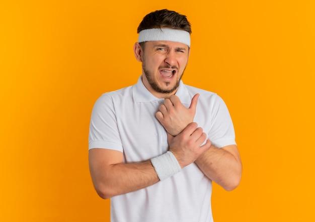 オレンジ色の壁の上に立っている痛みを持っている手首に触れる前を見てヘッドバンドと白いシャツの若いフィットネス男
