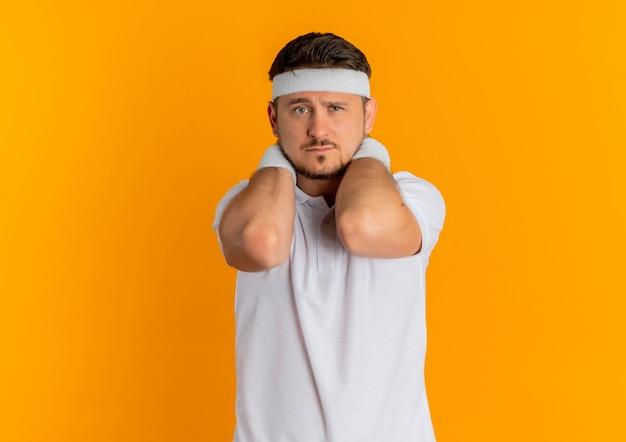 오렌지 벽 위에 서있는 얼굴에 슬픈 표정으로 앞을 찾고 머리띠와 흰 셔츠에 젊은 피트니스 남자
