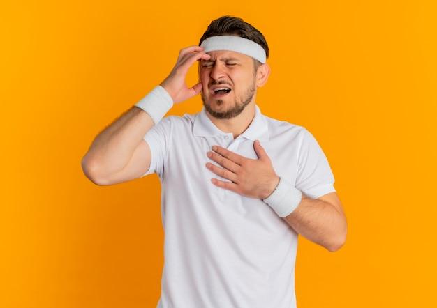 Молодой фитнес-мужчина в белой рубашке с повязкой на голове выглядит плохо с сильной головной болью, стоящей над оранжевой стеной
