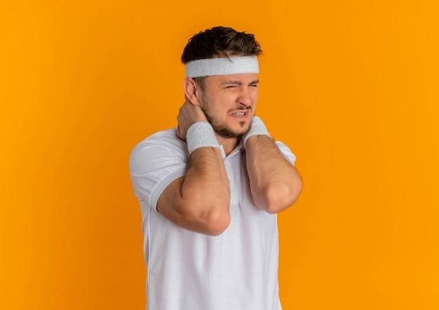 オレンジ色の壁の上に立っている痛みを感じて首に触れて気分が悪いヘッドバンドと白いシャツを着た若いフィットネス男