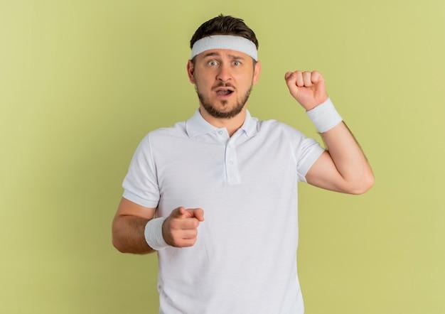 Молодой фитнес-мужчина в белой рубашке с повязкой на голову, указывая пальцем на передний кулак, выглядит удивленным, стоя над оливковой стеной