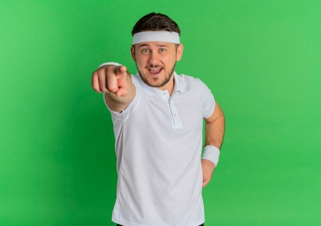 Молодой фитнес-мужчина в белой рубашке с повязкой на голову, указывая пальцем вперед, весело улыбаясь, стоя над зеленой стеной