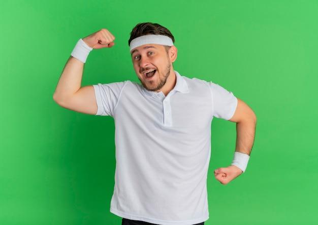 녹색 벽 위에 서 행복하고 흥분 팔뚝을 보여주는 주먹을 올리는 머리띠와 흰 셔츠에 젊은 피트니스 남자
