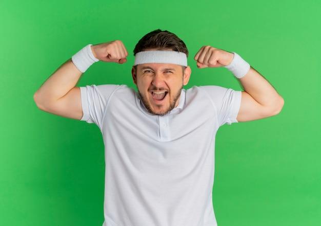 緑の壁の上に立って、幸せで興奮した上腕二頭筋を示す拳を上げるヘッドバンドと白いシャツの若いフィットネス男
