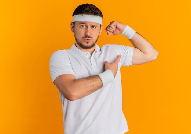Молодой фитнес-мужчина в белой рубашке с повязкой на голову, поднимающий кулак, демонстрирующий бицепс, уверенный и гордый вид, стоя над оранжевой стеной