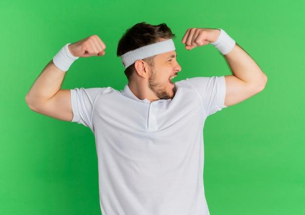 팔뚝을 보여주는 주먹을 올리는 머리띠와 흰 셔츠에 젊은 피트니스 남자