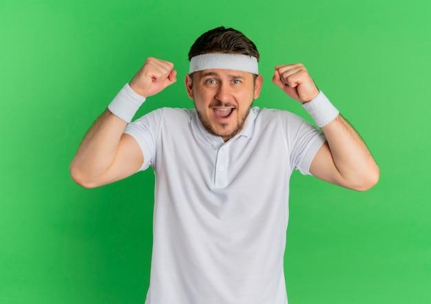 Молодой фитнес-мужчина в белой рубашке с повязкой на голову, поднимая кулаки, счастлив и взволнован, стоя у зеленой стены