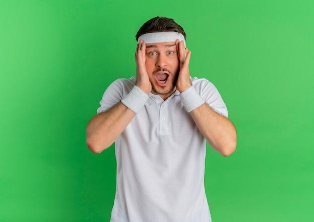 Молодой фитнес-мужчина в белой рубашке с повязкой на голове потрясен, держа голову над зеленой стеной