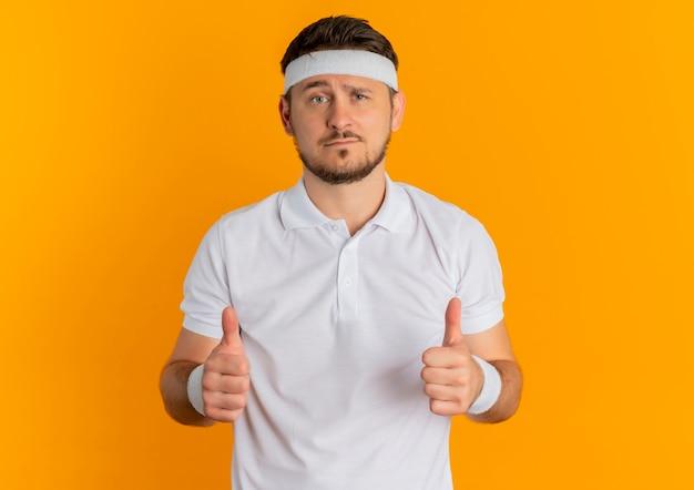 Молодой фитнес-мужчина в белой рубашке с повязкой на голову показывает палец вверх, глядя вперед, стоя над оранжевой стеной