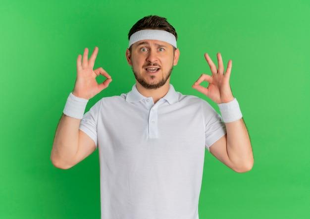 Молодой фитнес-мужчина в белой рубашке с повязкой на голове, улыбаясь, делает хорошо знаком с обеими руками, стоя над зеленой стеной