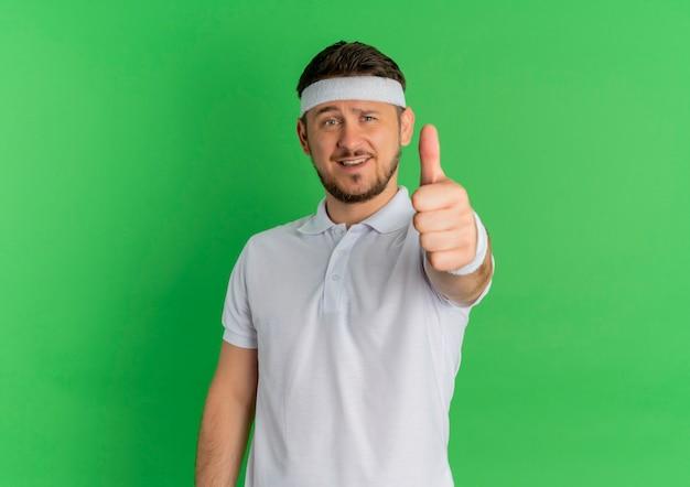 Молодой фитнес-мужчина в белой рубашке с повязкой на голову, улыбаясь, глядя вперед, показывает палец вверх, стоя над зеленой стеной