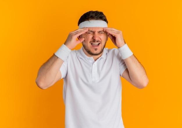 オレンジ色の壁の上に立っている痛みに苦しんで体調不良に見える寺院に触れるヘッドバンドと白いシャツの若いフィットネス男