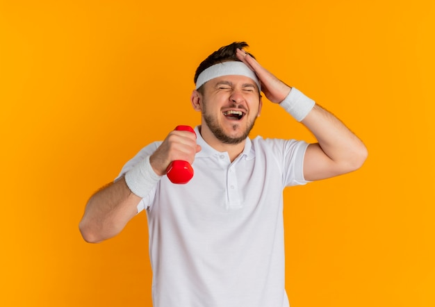 混乱しているように見えるダンベルで運動しているヘッドバンドと白いシャツを着た若いフィットネス男、オレンジ色の壁の上に立っているのを忘れた