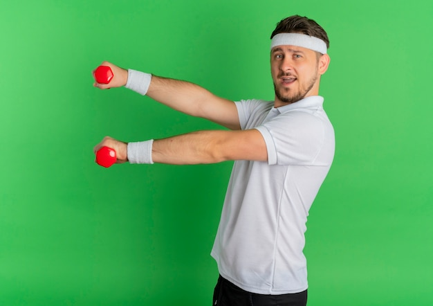 녹색 벽 위에 행복하고 긍정적 인 서 아령으로 운동하는 머리띠와 흰 셔츠에 젊은 피트니스 남자