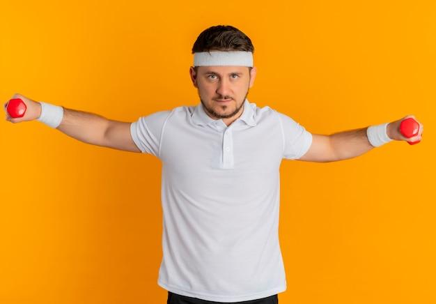 Молодой фитнес-мужчина в белой рубашке с повязкой на голову, тренирующийся с гантелями, уверенно смотрит, стоя над оранжевой стеной