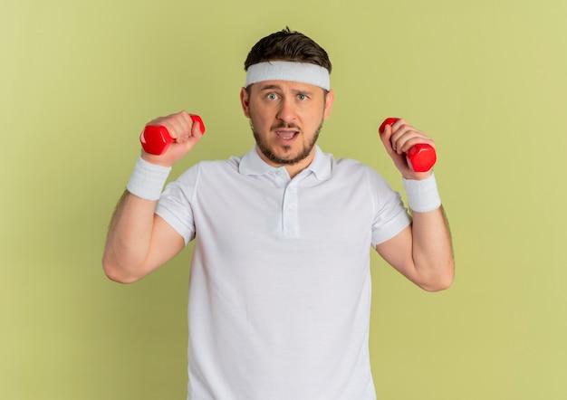 Молодой фитнес-мужчина в белой рубашке с повязкой на голову, тренирующийся с гантелями, выглядит смущенным, стоя у оливковой стены