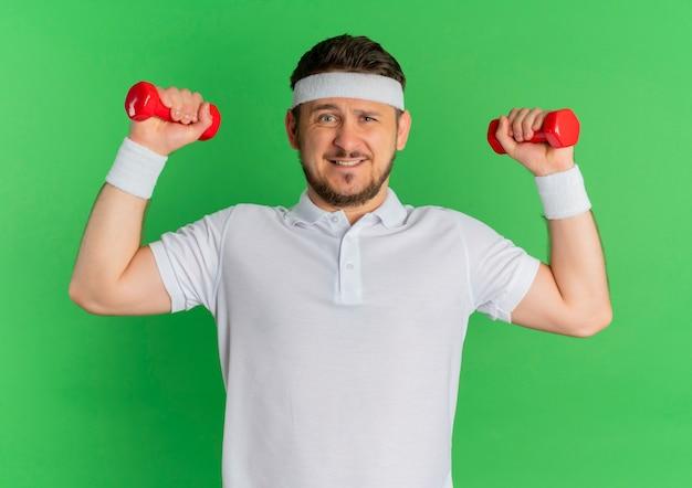 Молодой фитнес-мужчина в белой рубашке с повязкой на голове тренируется с напряженными и уверенными гантелями, стоя у зеленой стены
