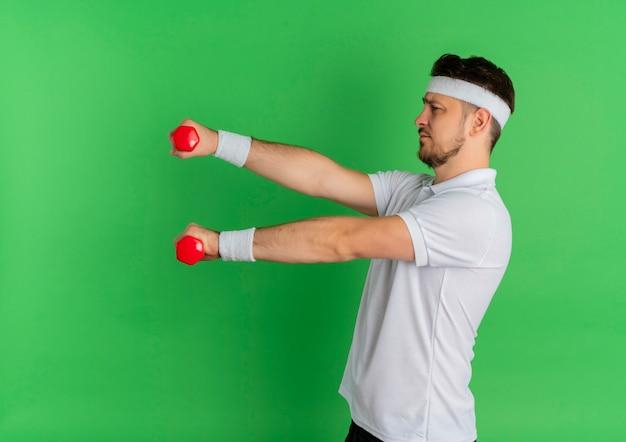 녹색 벽 위에 서있는 아령으로 운동하는 머리띠와 흰 셔츠에 젊은 피트니스 남자