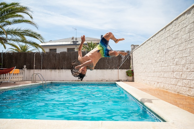 Young fitness man jumping into the water in the pool one day of summer vacation