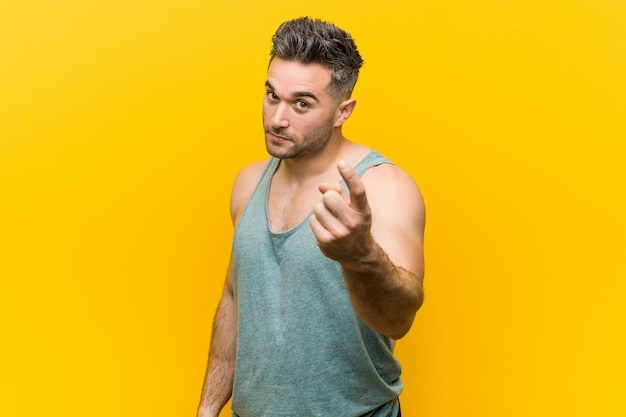 Young fitness man pointing with finger at you as if inviting come closer.