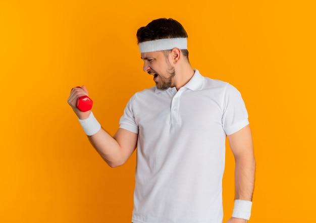 Giovane uomo fitness in camicia bianca con archetto facendo esercizi con manubri cercando in piedi teso su sfondo arancione