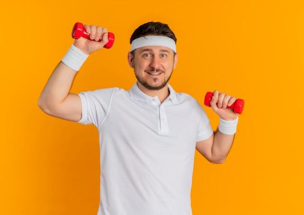 Giovane uomo fitness in camicia bianca con archetto facendo esercizi con manubri guardando la telecamera con il sorriso sul viso in piedi su sfondo arancione
