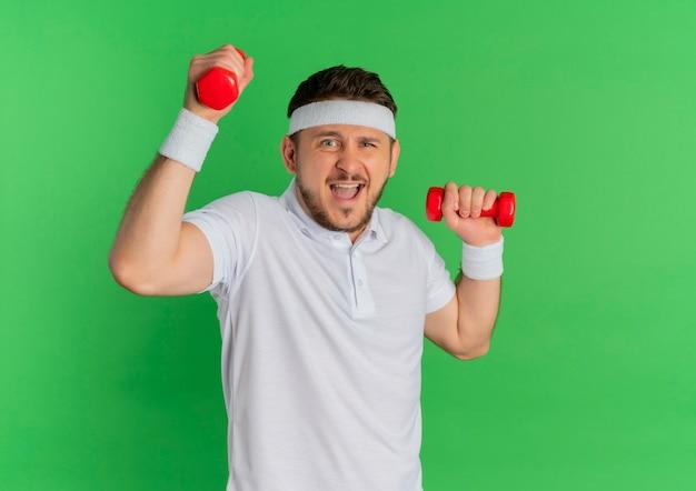 Giovane uomo di forma fisica in camicia bianca con archetto facendo esercizi con manubri cercando confuso in piedi su sfondo verde