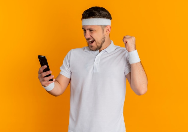 Giovane uomo fitness in camicia bianca con fascia golding smartphone pugno di serraggio felice ed eccitato in piedi su sfondo arancione