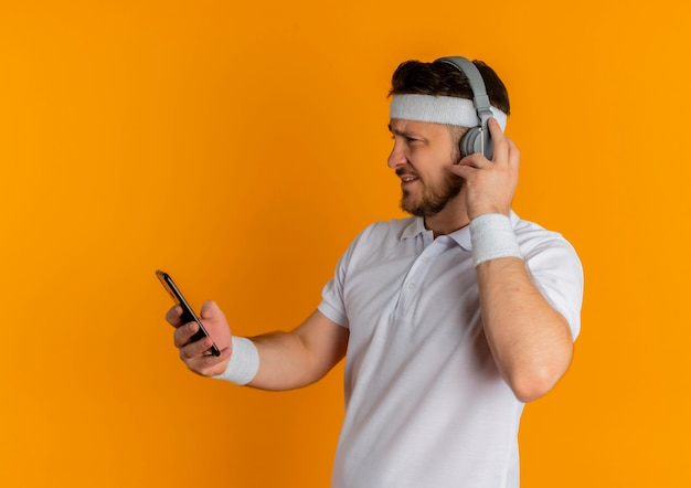 Young fitness man in white shirt with headband and headphones looking at screen of his mobile searching music standing over orange background