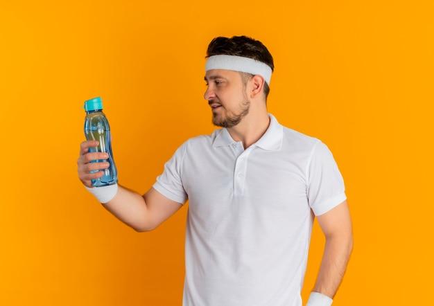 Giovane uomo di forma fisica in camicia bianca con la fascia tenendo la bottiglia di acqua guardandolo in piedi su sfondo arancione