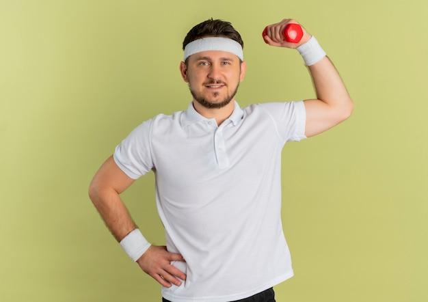 Giovane uomo fitness in camicia bianca con fascia tenendo il manubrio facendo esercizi cercando fiducioso in piedi su sfondo verde oliva