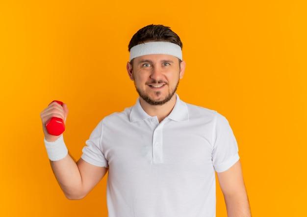 Giovane uomo fitness in camicia bianca con archetto tenendo il manubrio guardando fiducioso con il sorriso sul viso in piedi su sfondo arancione