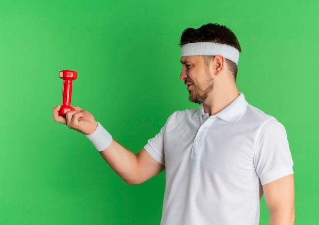 Giovane uomo fitness in camicia bianca con fascia tenendo il manubrio guardandolo confuso in piedi su sfondo verde