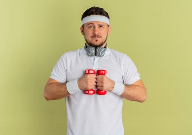 Giovane uomo fitness in camicia bianca con fascia tenendo i manubri facendo esercizi cercando fiducioso in piedi su sfondo verde oliva