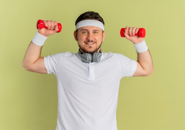 Giovane uomo fitness in camicia bianca con fascia tenendo i manubri facendo esercizi lsmiling fiducioso in piedi su sfondo verde oliva